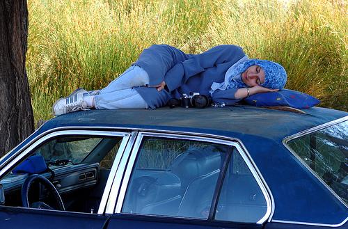 mujer durmiendo sobre un coche